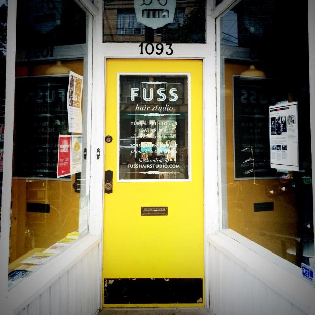 Yellow door of FUSS Hair Studio in Leslieville Toronto