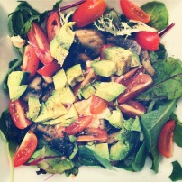 Spinach salad with sautéed mushrooms, avocado & grape tomatoes.